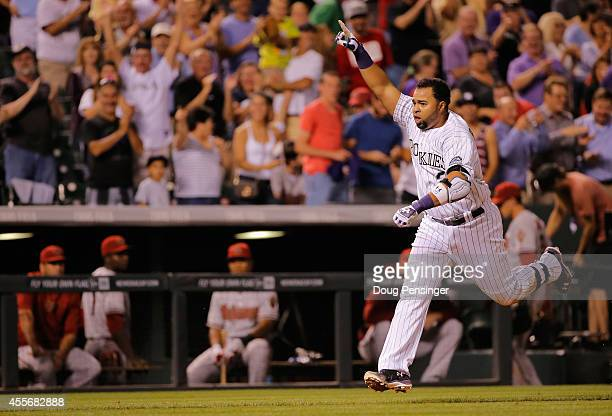 Wilin Rosario of the Colorado Rockies celebrates as he comes home to score on his game winning walk off two run home run off of Addison Reed of the...
