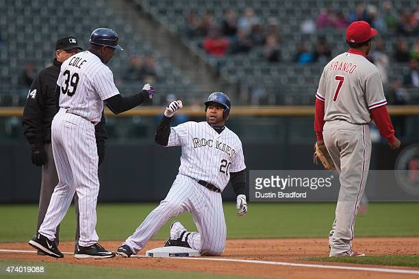 Wilin Rosario of the Colorado Rockies celebrates with third base coach Stu Cole after hitting a 2RBI triple against the Philadelphia Phillies in the...