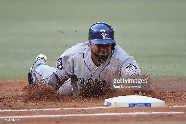 Wilin Rosario of the Colorado Rockies dives back to first base to avoid being doubled off in the third inning during MLB game action against the...