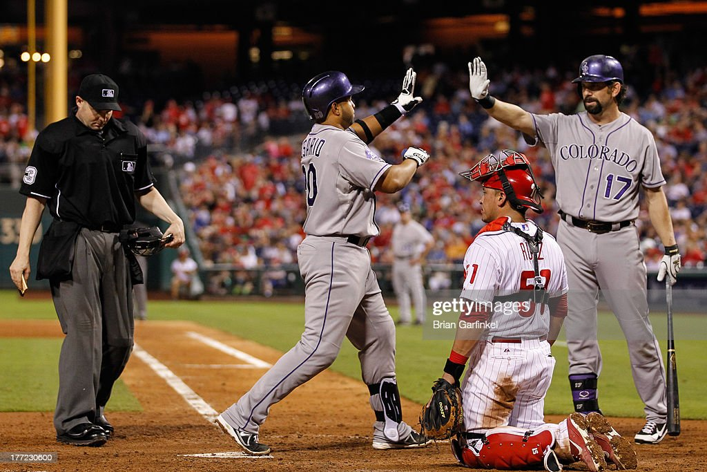 Wilin Rosario #20 of the Colorado Rockies is congratulated by Todd Helton #17 after Rosario hit a three run home run in the sixth inning of the game against the Philadelphia Phillies at Citizens Bank Park on August 22, 2013 in Philadelphia, Pennsylvania. The Phillies won 5-4.