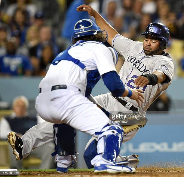 Wilin Rosario of the Colorado Rockies is tagged out at the plate by Yasmani Grandal of the Los Angeles Dodgers during the fourth inning at Dodger...