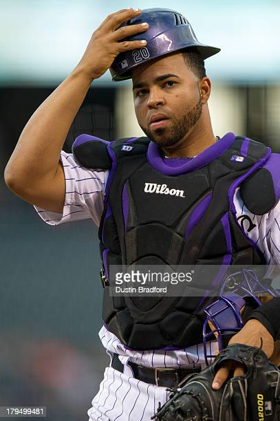 Wilin Rosario of the Colorado Rockies puts his batting helmet on before catching the first inning of a game against the Cincinnati Reds at Coors...