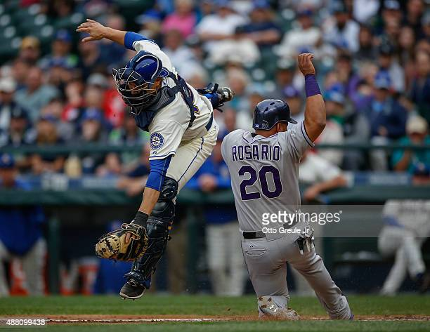 Wilin Rosario of the Colorado Rockies scores from third against catcher Steve Baron of the Seattle Mariners in the fourth inning at Safeco Field on...