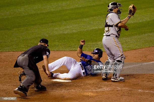 Wilin Rosario of the Colorado Rockies scores the winning run in the ninth inning under the watchful eye of home plate umpire Mike Muchlinski while...