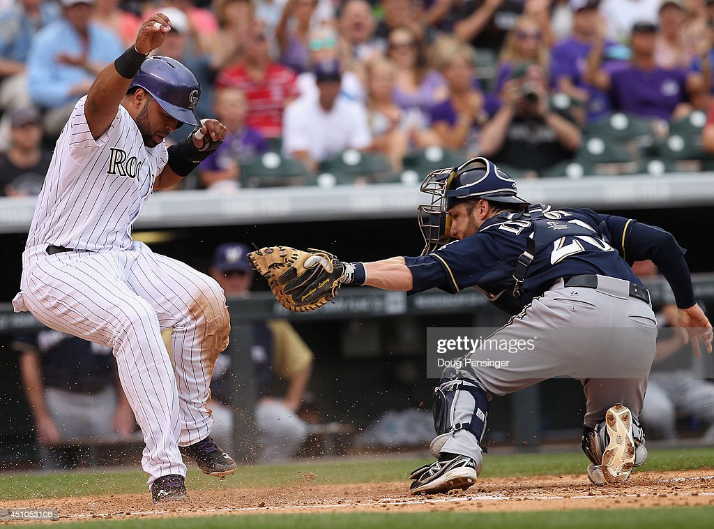 Wilin Rosario #20 of the Colorado Rockies slides around catcher Jonathan Lucroy #20 of the Milwaukee Brewers to score on a single by Charlie Blackmon #19 of the Colorado Rockies as they Brewers held a 3-1 lead in the second inning at Coors Field on June 22, 2014 in Denver, Colorado.