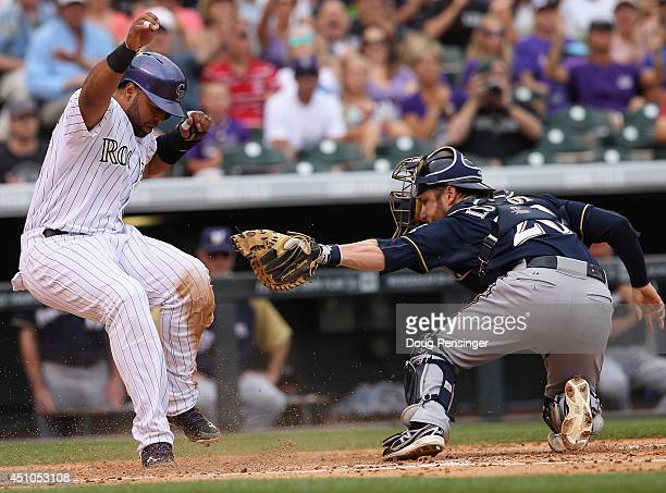 Wilin Rosario of the Colorado Rockies slides around catcher Jonathan Lucroy of the Milwaukee Brewers to score on a single by Charlie Blackmon of the...