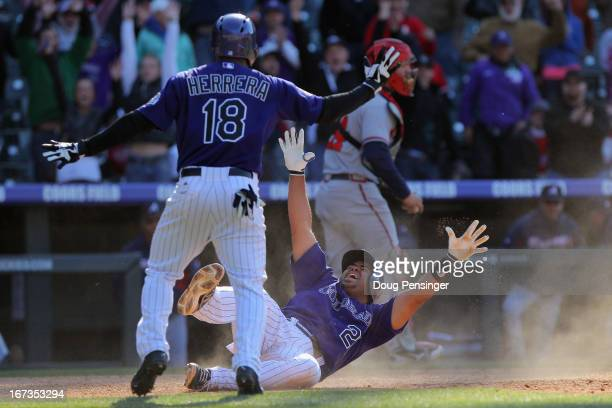Wilin Rosario of the Colorado Rockies slides home with the winning run and celebrates with Jonathan Herrera of the Colorado Rockies on a single by...