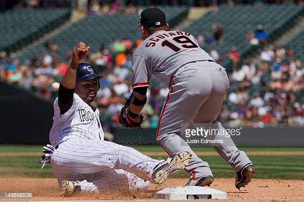 Wilin Rosario of the Colorado Rockies slides into third base after advancing on a base hit by Jonathan Herrera as third baseman Marco Scutaro of the...