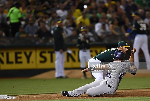 Wilin Rosario of the Colorado Rockies slides into third base safe beating the throw to Brett Lawrie of the Oakland in the top of the seventh inning...