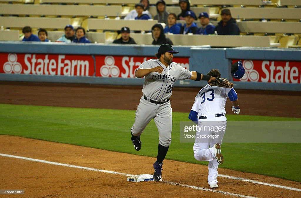 Wilin Rosario #20 of the Colorado Rockies tags out and knocks off the helmet of Scott Van Slyke #33 of the Los Angeles Dodgers at first base for the second out of the third inning during the MLB game at Dodger Stadium on May 14, 2015 in Los Angeles, California.