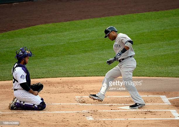 Wilin Rosario of the Colorado Rockies watches Robinson Cano of the New York Yankees touch home plate his home run in the fifth inning off of Adam...