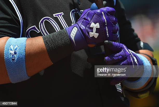Wilin Rosario of the Colorado Rockies wearing Under Armour batting gloves holds onto his bat in the ondeck circle against the San Francisco Giants at...