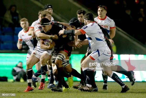 Will Addison and Rob Webber of Sale Sharks tackled by Francois Van Der Merwe of Lyon during the European Rugby Challenge Cup match between Sale...