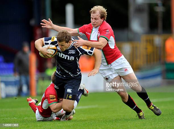 Will Addison of Sale Sharks is tackled by Chris Banfield and Michael Hills of London Welsh during the JP Morgan Asset Management Premiership Rugby...