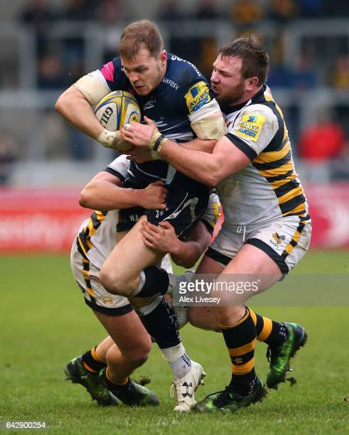Will Addison of Sale Sharks is tackled by Matt Mullan and Tommy Taylor of Wasps during the Aviva Premiership match between Sale Sharks and Wasps at...