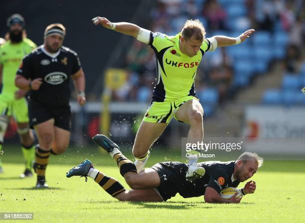 Will Addison of Sale Sharks jumps over Dan Robson of Wasps during the Aviva Premiership match between Wasps and Sale Sharks at The Ricoh Arena on...