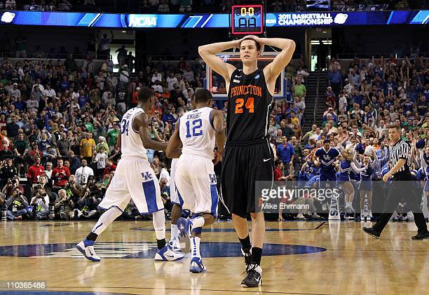 Will Barrett of the Princeton Tigers looks on dejected as Brandon Knight and DeAndre Liggins of the Kentucky Wildcats celebrate their 5957 win during...