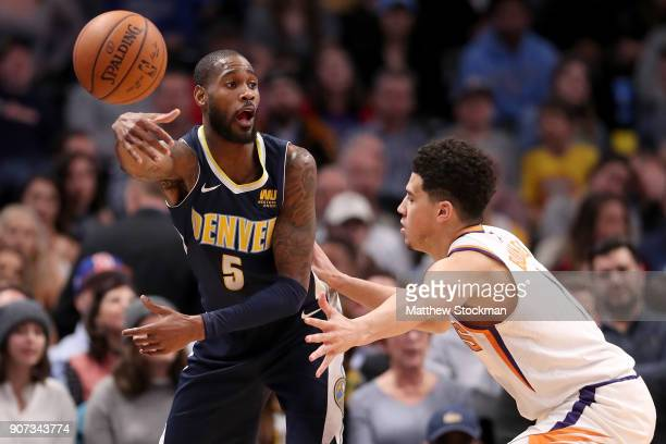Will Barton of the Denver Nuggets passe the ball while being guarded by Devin Booker of the Phoenix Suns at the Pepsi Center on January 19 2018 in...