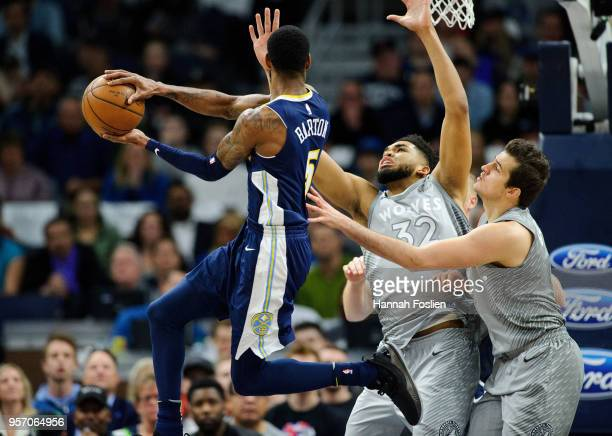 Will Barton of the Denver Nuggets passes the ball away from KarlAnthony Towns and Nemanja Bjelica of the Minnesota Timberwolves during the game on...
