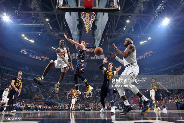 Will Barton of the Denver Nuggets passes the ball to Paul Millsap of the Denver Nuggets against the Cleveland Cavaliers on March 7 2020 at Rocket...