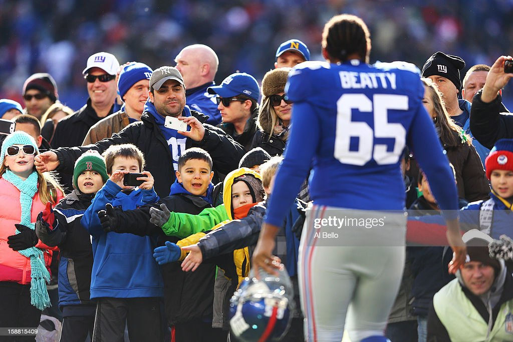 Will Beatty #65 of the New York Giants greets families of Sandy Hook Elementary School before the game against the Philadelphia Eagles their game against the at MetLife Stadium on December 30, 2012 in East Rutherford, New Jersey.