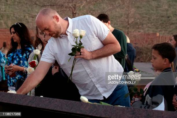 Will Beck a Columbine High School massacre survivor reacts while placing flowers at the Columbine Memorial at Clement Park in Littleton Colorado...