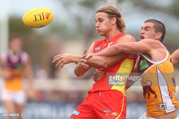 Will Brodie of the Suns is tackled by Tom Rockliff of the Lions during the 2017 JLT Community Series match at Broadbeach Sports Centre on February 19...