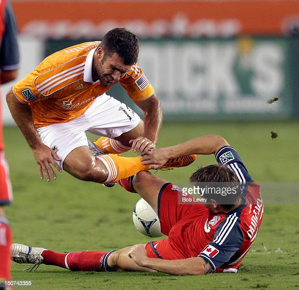 Will Bruin of the Houston Dynamo is tripped up by Terry Dunfield of the Toronto FC in the first half at BBVA Compass Stadium on August 25 2012 in...