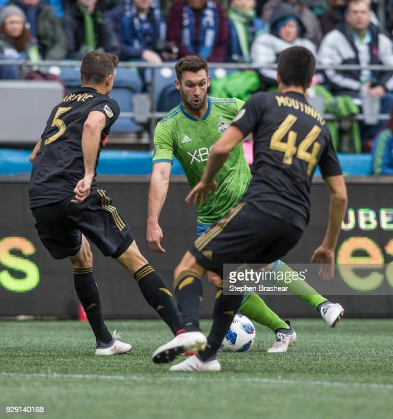 Will Bruin of the Seattle Sounders tries to dribble through Dejan Jakovic of Los Angeles FC and Moutinho Joao of Los Angeles FC during a match at...