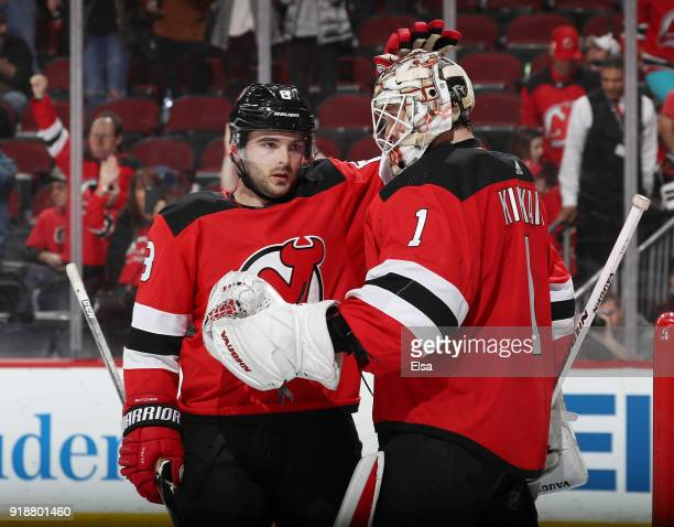 Will Butcher celebrates the win with teammate Keith Kinkaid of the New Jersey Devils after the game against the Carolina Hurricanes on February 15...