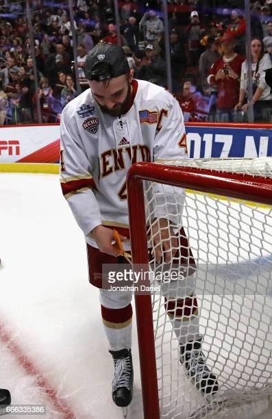 Will Butcher of the Denver Pioneers cuts the net after a win over the MinnesotaDuluth Bulldogs during the 2017 NCAA Division I Men's Ice Hockey...