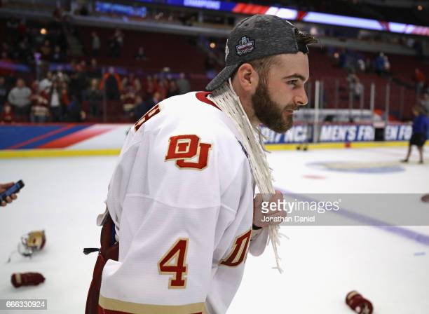 Will Butcher of the Denver Pioneers wears a peice of the net around his neck following a win over Minnesota-Duluth Bulldogs during the 2017 NCAA...