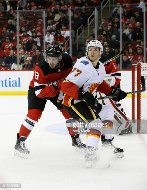 Will Butcher of the New Jersey Devils and Mark Jankowski of the Calgary Flames battle for position during the game at Prudential Center on February 8...