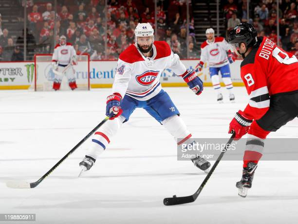 Will Butcher of the New Jersey Devils attempts to clear the puck past Nate Thompson of the Montreal Canadiens during the second period on February 4...