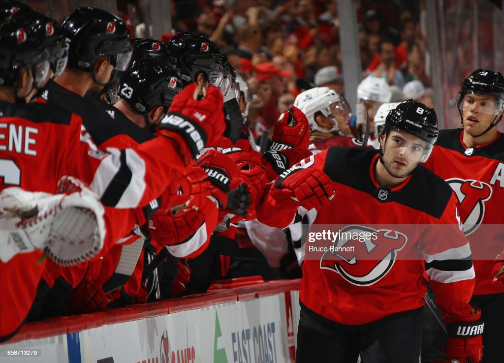 Will Butcher #8 of the New Jersey Devils celebrates his first NHL point as he registers an assist on a first-period goal by Adam Henrique #14 against the Colorado Avalanche at the Prudential Center on October 7, 2017 in Newark, New Jersey.