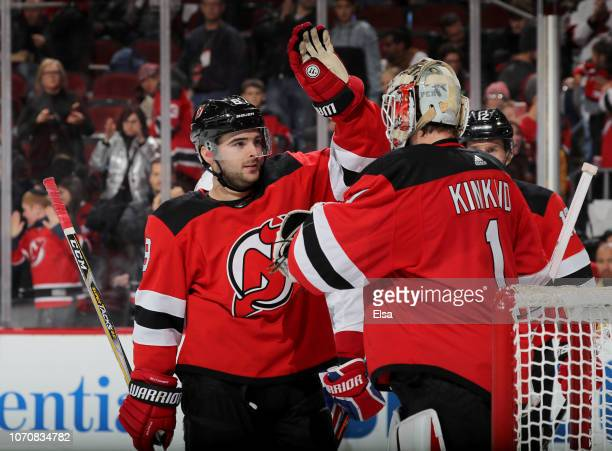 Will Butcher of the New Jersey Devils congratulates Keith Kinkaid after the game against the Montreal Canadiens at Prudential Center on November 21...