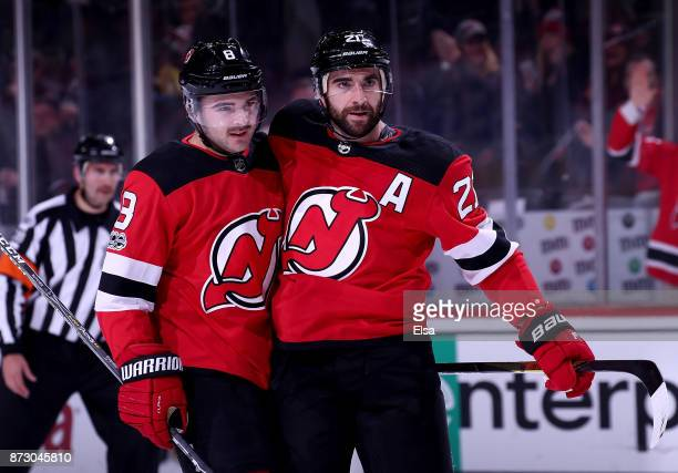 Will Butcher of the New Jersey Devils congratulates teammate Kyle Palmieri after he scored in the second period against the Florida Panthers on...