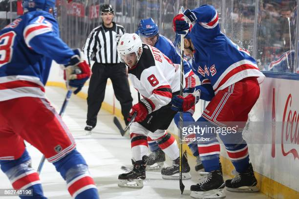 Will Butcher of the New Jersey Devils skates against Kevin Shattenkirk and JT Miller of the New York Rangers at Madison Square Garden on October 14...