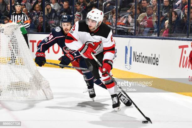 Will Butcher of the New Jersey Devils skates the puck away from Tyler Motte of the Columbus Blue Jackets during the first period of a game on...