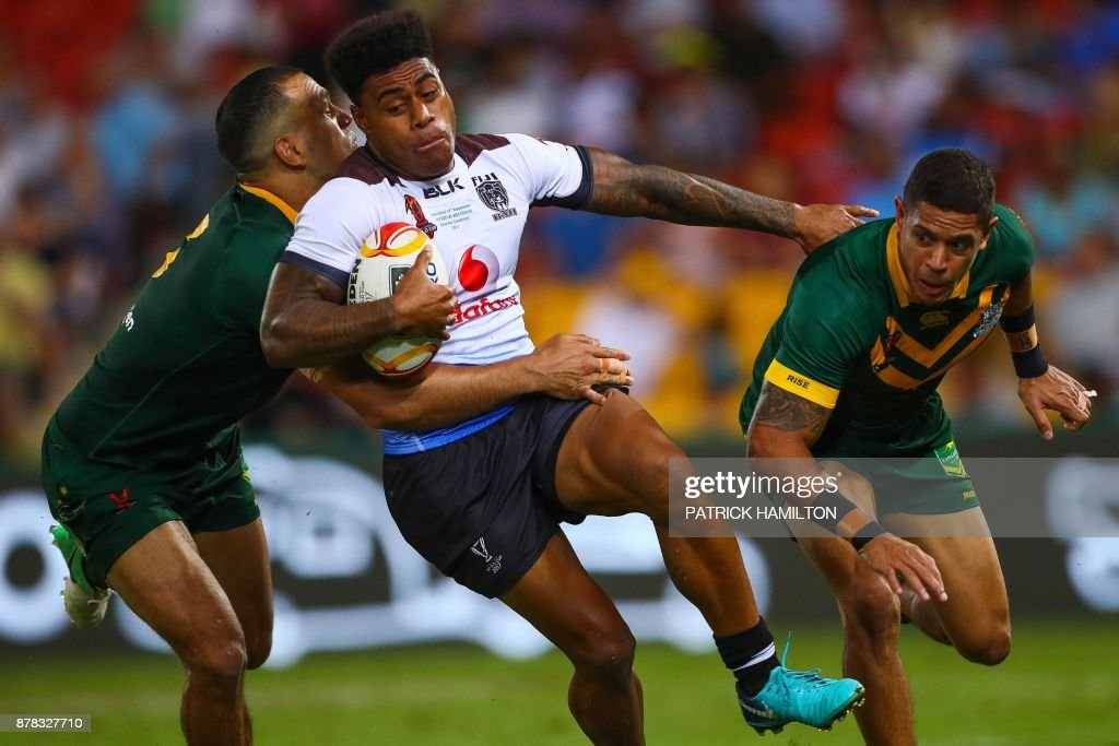 TOPSHOT - Will Chambers (L) and Dane Gagai (R) of Australia attempt to tackle Henry Raiwalui of Fiji during the Rugby League World Cup men's semi-final match between Australia and Fiji at the Suncorp Stadium in Brisbane on November 24, 2017. / AFP PHOTO / Patrick HAMILTON / --IMAGE