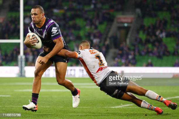 Will Chambers of the Melbourne Storm beats the tackle of Moses Mbye of the Tigers to score the match winning try during the round 10 NRL match...