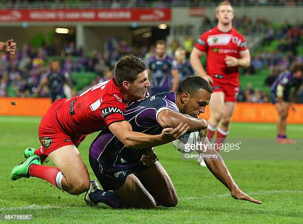 Will Chambers of the Storm breaks through a tackle by Gareth Widdop of the Dragons to score a try during the round 6 NRL match between the Melbourne...