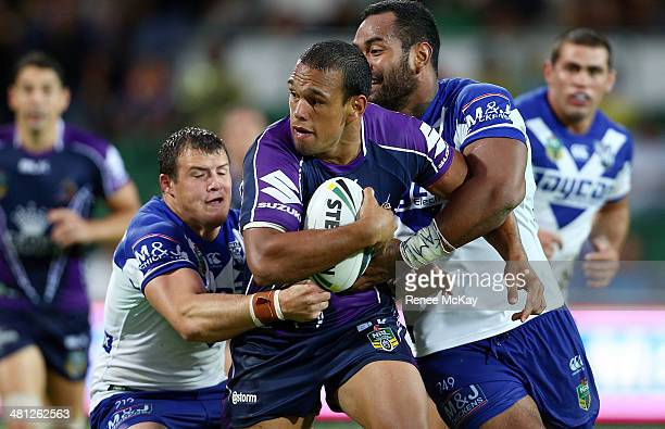 Will Chambers of the Storm is tackled by Josh Morris and Tony Williams during the round four NRL match between the CanterburyBankstown Bulldogs and...
