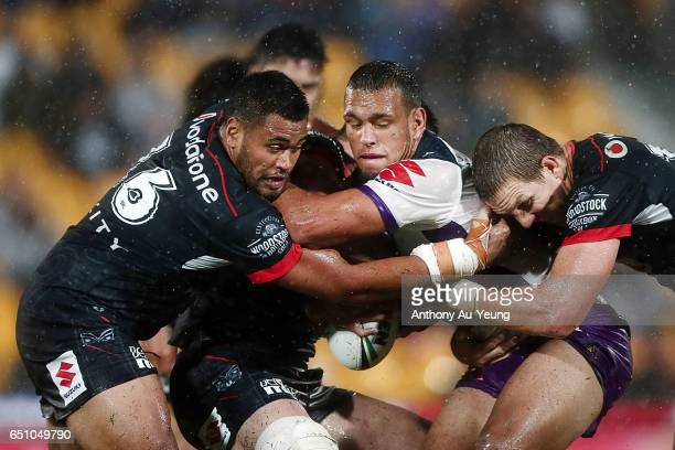 Will Chambers of the Storm is tackled by Ryan Hoffman and Sam Lisone of the Warriors during the round two NRL match between the New Zealand Warriors...