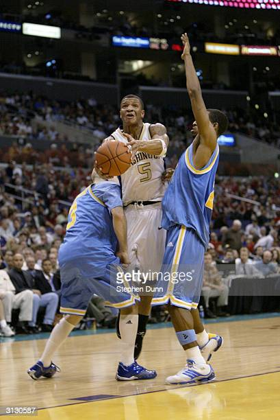 Will Conroy of the Washington Huskies is covered by Brian Morrison and Cedric Bozeman of the UCLA Bruins during the quarterfinals of the 2004 Pacific...