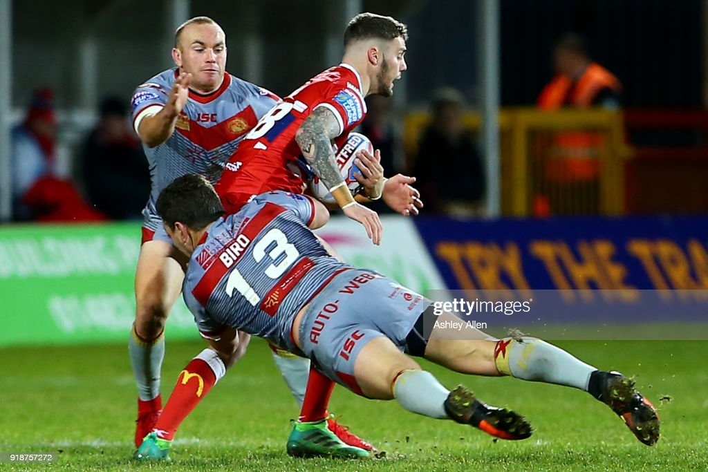 Will Dagger of Hull KR is tackled by Greg Bird and Luke Walsh of the Catalans Dragons during the BetFred Super League match between Hull KR and Catalans Dragons at KCOM Craven Park on February 15, 2018 in Hull, England.