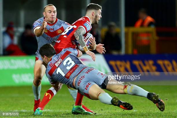 Will Dagger of Hull KR is tackled by Greg Bird and Luke Walsh of the Catalans Dragons during the BetFred Super League match between Hull KR and...