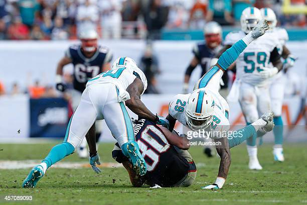Will Davis and Reshad Jones of the Miami Dolphins tackle Danny Amendola of the New England Patriots on the final drive of the game on December 15...