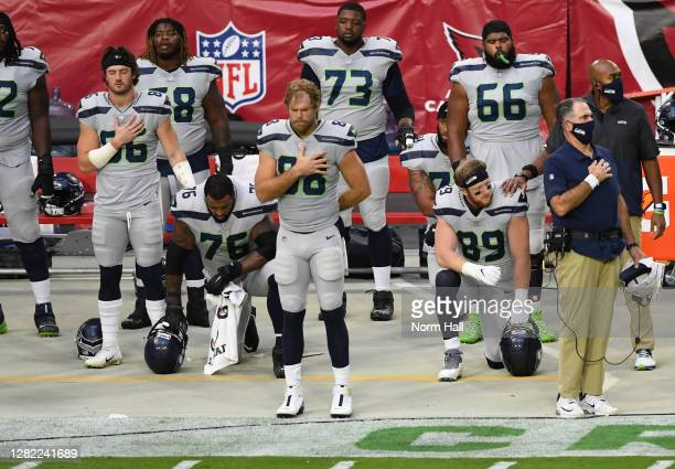 Will Dissly and Duane Brown of the Seattle Seahawks kneel during the singing of the national anthem while surrounded by teammates prior to a game...