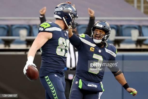 Will Dissly of the Seattle Seahawks celebrates with Russell Wilson after scoring a 10 yard touchdown against the New York Jets during the third...